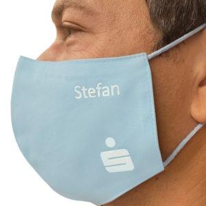 Die Maske aufgesetzt mit Logo und Namen des Mitarbeiters bedruckt